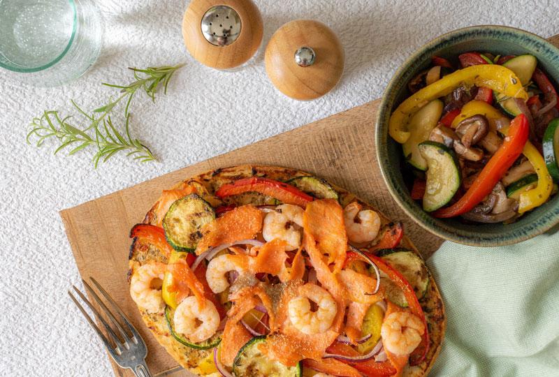 Naanpizza met gegrilde groenten, gerookte zalm en roze garnalen